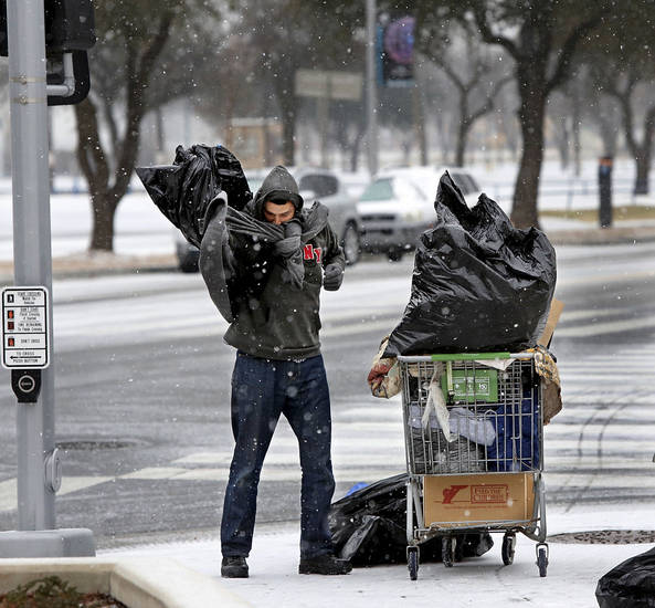 A man covers himself with a trash bag to block the blowing snow Tuesday as he leaves the Red Andrews Christmas Dinner in Oklahoma City. Photo by  Jim Beckel,  The Oklahoman