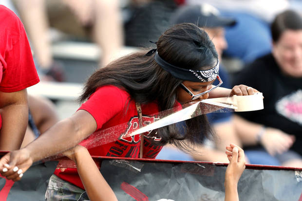 Carl Albert senior Tara Satterwhite tapes a banner to the stands before a high school football game between the Carl Albert Titans and the Deer Creek Antlers on Friday, Sept. 27, 2013 in Midwest City, Okla. Photo by Steve Sisney, The Oklahoman
