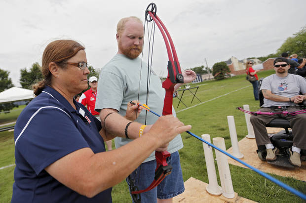 Coach Randi Smith, left, helps first time participant Jeff Hudgens load an arrow in the archery clinic during the opening day of activities for the Endeavor Games at the University of Central Oklahoma on Thursday, June 6, 2013 in Edmond, Okla. Photo by Chris Landsberger, The Oklahoman