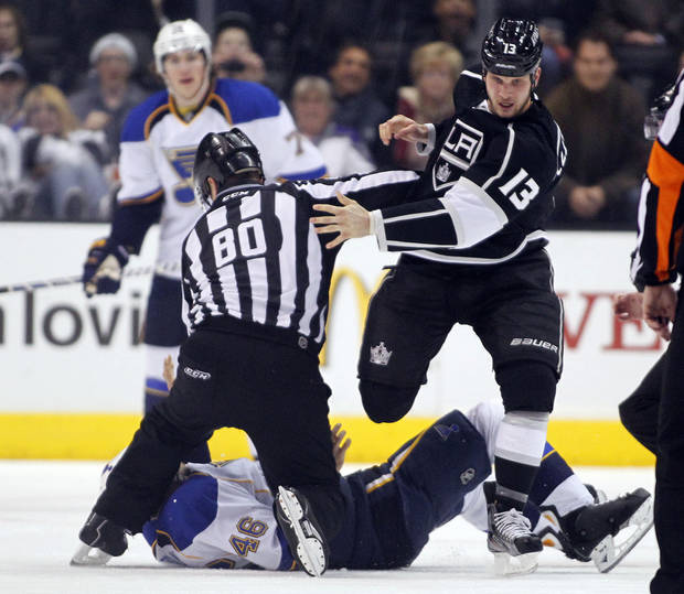 Los Angeles Kings left wing Kyle Clifford (13) steps over St. Louis Blues defenseman Roman Polak (46), of the Czech Republic, after forcing Polak to the ice during a fight in the first period of an NHL hockey game Tuesday, March 5, 2013, in Los Angeles.  Linesman Thor Nelson (80) protects Polak from further injury on the ice. (AP Photo/Alex Gallardo)
