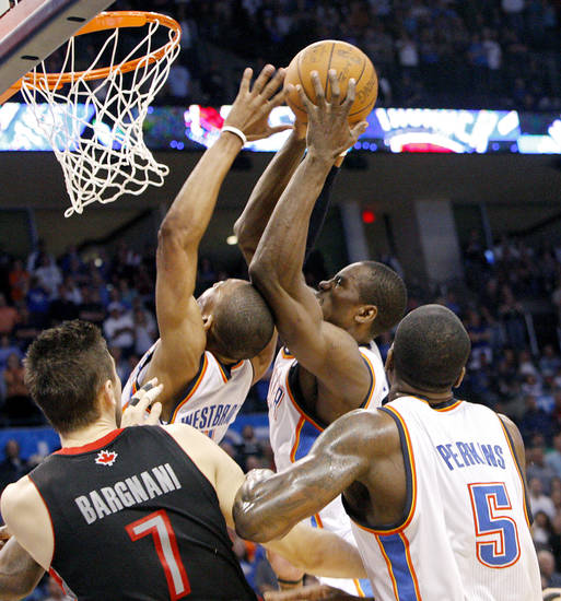 Oklahoma City's Serge Ibaka and Russell Westbrrok fight over a rebound  during the second half of their NBA basketball game against Toronto at the OKC Arena in downtown Oklahoma City on Sunday, March 20, 2011. The Raptors beat the Thunder 95-93. Photo by John Clanton, The Oklahoman