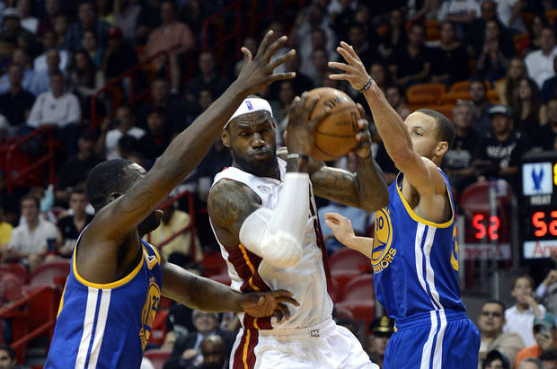 Miami Heat's LeBron James, center, is defended by Golden State Warriors' Draymond Green (23) and Stephen Curry (30) during an NBA basketball game on Wednesday, Dec. 12, 2012, in Miami. (AP Photo/Rhona Wise)