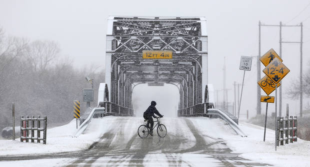 A bicyclist rides over the Route 66 bridge at Lake Overholser in Oklahoma City, Tuesday February 04, 2014. Photo By Steve Gooch, The Oklahoman