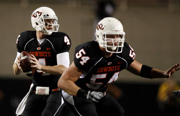 OSU's Brandon Weedon (4) looks to pass as Andrew Lewis (54) blocks during the college football game between Oklahoma State University (OSU) and the University of Colorado (CU) at Boone Pickens Stadium in Stillwater, Okla., Thursday, Nov. 19, 2009. Photo by Sarah Phipps, The Oklahoman