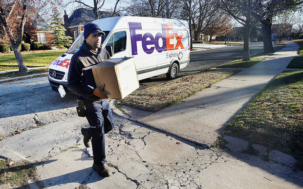 FedEx courier Kendall Ellis delivers packages Monday in northwest Oklahoma City. FedEx expected to set a record for number of packages delivered Monday.