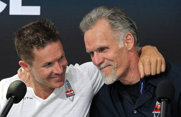 Felix Baumgartner, left, of Austria, and Art Thompson, technical project director, hug one another after Baumgartner successfully jumped from a space capsule lifted by a helium balloon at a height of just over 128,000 feet above the Earth's surface, Sunday, Oct. 14, 2012, in Roswell, N.M. (AP Photo/Ross D. Franklin) ORG XMIT: NMRF131