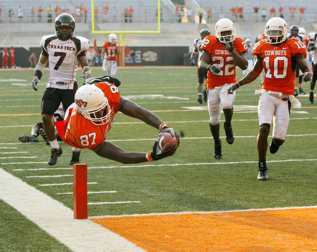 OSU's Brandon Pettigrew (87) dives into the end zone for a touchdown in front of Texas Tech's Darcel McBath (7) and OSU's Dantrell Savage (22) and Tommy Devereaux (10) in the fourth quarter of the college football game between the Oklahoma State University Cowboys (OSU) and the Texas Tech University Red Raiders (TTU) at Boone Pickens Stadium in Stillwater, Okla., on Saturday, Sept. 22, 2007. OSU won, 49-45. Pettigrew's touchdown was the go-ahead score for the Cowboys. By NATE BILLINGS, The Oklahoman