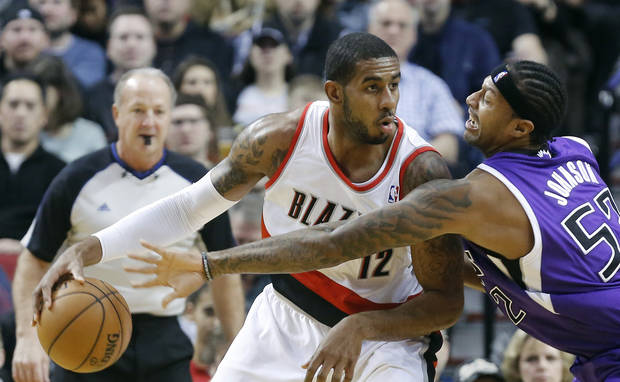 Portland Trail Blazers forward LaMarcus Aldridge, left, works the ball in against Sacramento Kings forward James Johnson during the first quarter of an NBA basketball game in Portland, Ore., Wednesday, Dec. 26, 2012. (AP Photo/Don Ryan)