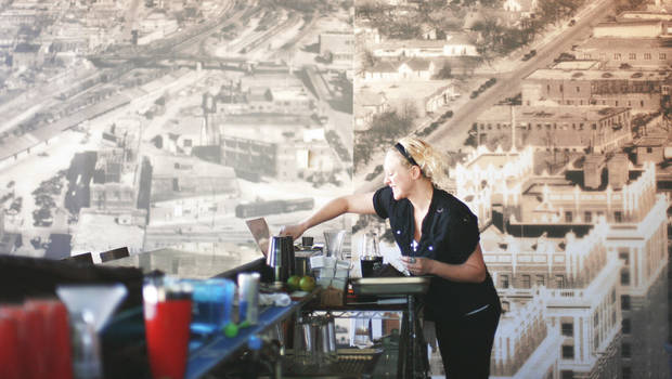 Courtney Pope prepares a drink at the Sage Gourmet Market and Cafe, where the history of Deep Deuce is shown in a wall-size mural. PHOTO BY BRYAN TERRY, THE OKLAHOMAN