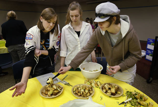 From left, Katelyn Kordic, 15, Julianna Straughn, 13, and her sister Katie, 16, fill pie crusts at an apple pie baking workshop at the Norman Public Library.  PHOTO BY STEVE SISNEY, THE OKLAHOMAN
