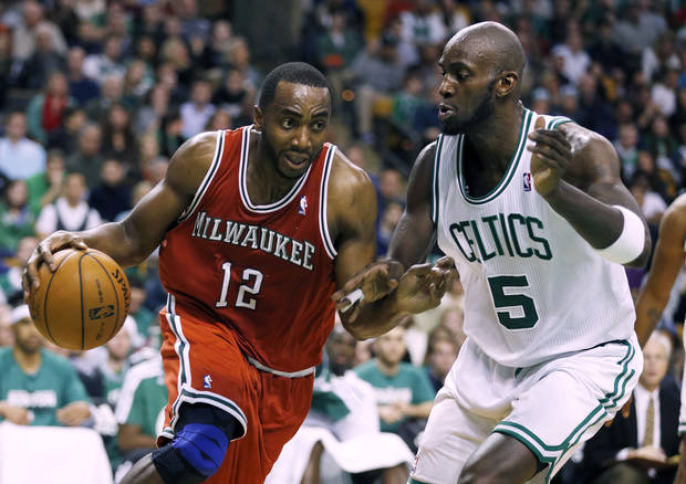Milwaukee Bucks' Luc Richard Mbah a Moute (12) drives past Boston Celtics' Kevin Garnett (5) in the fourth quarter of an NBA basketball game in Boston, Friday, Dec. 21, 2012. The Bucks won 99-94 in overtime. (AP Photo/Michael Dwyer)