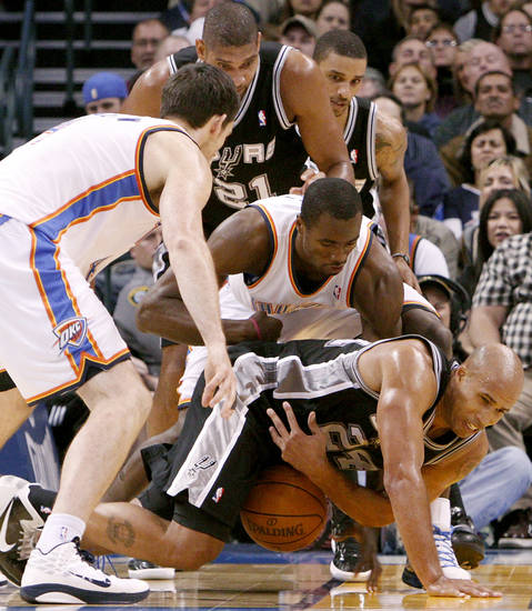 Oklahoma City's Serge Ibaka battles with San Antonio's Richard Jefferson (bottom) and Tim Duncan for a loose ball during their NBA basketball game in downtown Oklahoma City  on Sunday, Nov. 14, 2010. The Thunder lost to the Spurs 117-104. Photo by John Clanton, The Oklahoman