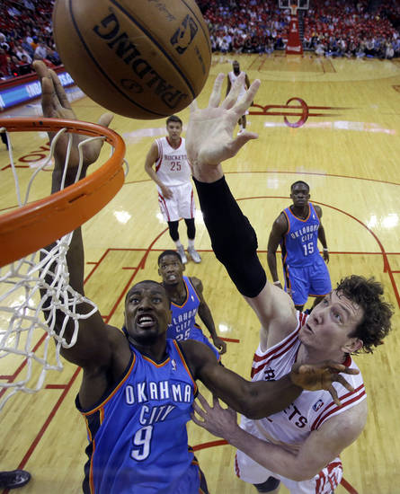Houston Rockets' Omer Asik (3) shoots as Oklahoma City Thunder's Serge Ibaka (9) defends during the first quarter of Game 4 in their first-round NBA basketball playoff series Monday, April 29, 2013, in Houston. (AP Photo/David J. Phillip)