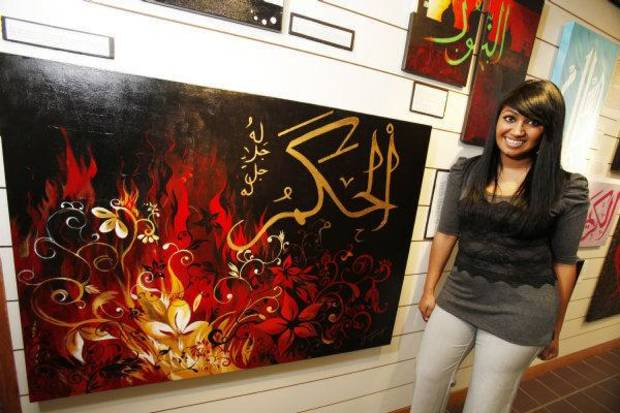 Artist Farzana Jahangir poses with her painting, which is part of a display at the Midwest City Library. The display includes works by students of Mercy School, a Muslim school in Oklahoma City.