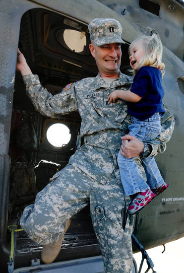 Capt. John Pollard carries daughter Reagan, 2, after showing her his helicopter before the deployment ceremony for the 149th General Support Aviation Battalion (GSAB), as they deploy to Afghanistan in support of Operation Enduring Freedom on Thursday, April 25, 2013 in Lexington, Okla.  Photo by Steve Sisney, The Oklahoman