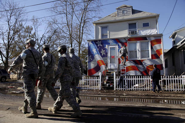 Members of the National Guard walk past a house damaged by Superstorm Sandy as it is painted with an American flag in the New Dorp section of Staten Island, New York, Tuesday, Nov. 6, 2012. Voting in the U.S. presidential election is the latest challenge for the hundreds of thousands of people in the New York-New Jersey area still affected by Superstorm Sandy.  (AP Photo/Seth Wenig) ORG XMIT: NYSW119