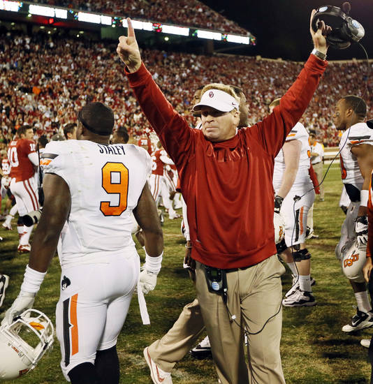 OU defensive coordinator Mike Stoops celebrates next to Oklahoma State's Kye Staley (9) after the Bedlam college football game between the University of Oklahoma Sooners (OU) and the Oklahoma State University Cowboys (OSU) at Gaylord Family-Oklahoma Memorial Stadium in Norman, Okla., Saturday, Nov. 24, 2012. OU won, 51-48 in overtime. Photo by Nate Billings , The Oklahoman