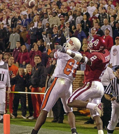 OSU receiver Rashaun Woods goes for a touchdown catch in front of OU's Derrick Strait in the fourth quarter of the Bedlam college football game between Oklahoma and Oklahoma State, Saturday Nov. 24, 2001, in Norman, Okla. Woods made the catch to win the game. OSU won, 16-13. Staff photo by Nate Billings.