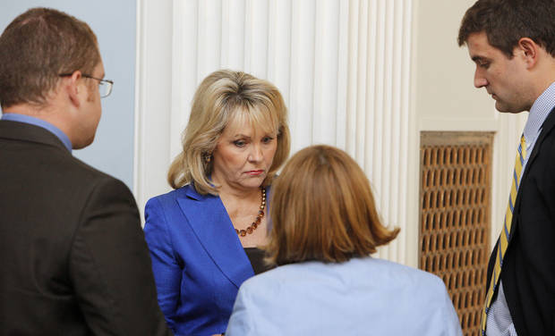 Gov. Mary Fallin huddles with her staff Thursday before talking with reporters on how the U.S. Supreme Court�s decision to uphold the federal health care law will affect Oklahoma. By Paul B. Southerland, The Oklahoma
