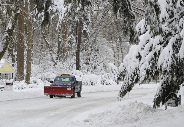 A pickup truck with a snow plow drives a snow-covered Bayville Road after a snow storm on Saturday, Feb. 9, 2013 in Lattingtown, N.Y. A howling storm across the Northeast left the New York-to-Boston corridor shrouded in 1 to 3 feet of snow Saturday, stranding motorists on highways overnight and piling up drifts so high that some homeowners couldn't get their doors open. More than 650,000 homes and businesses were left without electricity. (AP Photo/Kathy Kmonicek) ORG XMIT: NYKK119