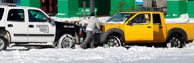 Oklahoma Highway Patrol Trooper Mike Roe pushes a motorist out of snow in a Midwest City parking lot. Many spent Christmas Day, Dc. 25, 2009,  digging out from record snow storm that dumped 14 inches of severe winter storm in the Oklahoma City area.   Photo by Jim Beckel, The Oklahoman