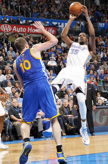 Oklahoma City�s Kevin Durant, right, takes a shot over Golden State�s David Lee on Sunday.  Photo by Garett Fisbeck, The Oklahoman