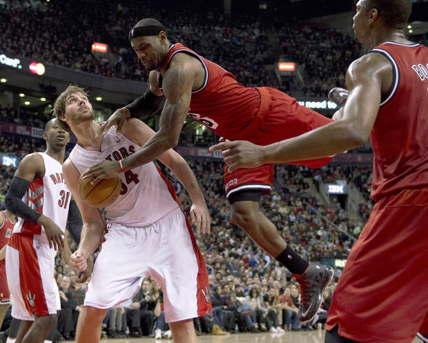 Miami Heat forward LeBron James, right, falls to the floor after trying to dunk over Toronto Raptors center Aaron Gray, left, during first half NBA action in Toronto on Sunday Feb. 3, 2013. (AP Photo/THE CANADIAN PRESS,Frank Gunn)