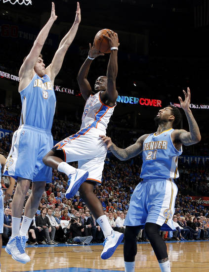Oklahoma City's Reggie Jackson (15) goes between Denver's Danilo Gallinari (8) and Wilson Chandler (21) during an NBA basketball game between the Oklahoma City Thunder and the Denver Nuggets at Chesapeake Energy Arena in Oklahoma City, Tuesday, March 19, 2013. Photo by Bryan Terry, The Oklahoman