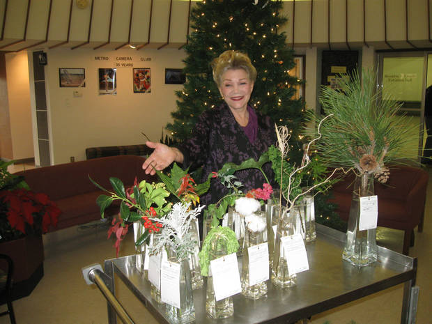 Flower show Chairman Diana Treat appraises some of the show&acirc;s horticulture entries. PHOTO BY PAULA BURKES, THE OKLAHOMAN