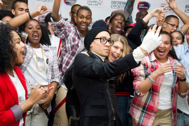 The Black Eyed Peas members Taboo, center left, and Fergie, center right, take their photo with students at the launch of a new Peapod Adobe Youth Voices Academy in New York, Tuesday, April 19, 2011. (AP Photo/Charles Sykes)