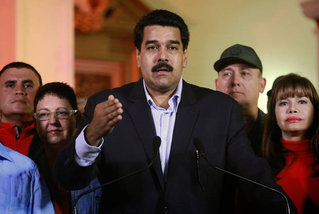 "In this photo released by Miraflores Press Office, Venezuela's Vice-President Nicolas Maduro, center, accompanied by other members of the cabinet, spekas for Venezuelan Television at the presidential palace in Caracas, Venezuela, Tuesday, Dec. 11, 2012. Maduro said Chavez was recovering in Cuba after an operation targeting an aggressive cancer that has defied multiple treatments. The operation was ""complex"" but was completed ""correctly and successfully,"" he said. (AP Photo/Miraflores Press Office, Francisco Batista)"