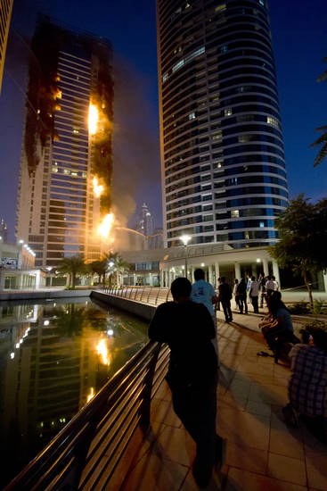 People watch flames engulf a portion of Tamweel residential tower at Jumeirah Lakes Towers, in Dubai, United Arab Emirates, Sunday, Nov. 18, 2012. Civil defense officials did not give immediate details on possible casualties or the cause of the predawn fire. (AP Photo/Kaveh Kashani)