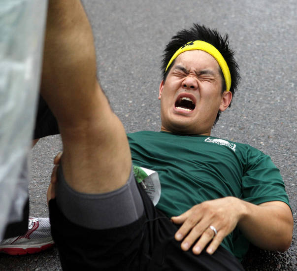 Andrew Hwang gets help with a cramp after finishing the Oklahoma City Memorial Marathon in Oklahoma City, Sunday, April 29, 2012. Photo by Bryan Terry, The Oklahoman