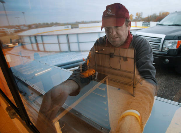 Doug Kennon, Sooner Legends owner, opens a window as he readies a concession stand for the outdoor ice skating rink at Marc Heitz Chevrolet on Tuesday, Nov. 22, 2011, in Norman, Okla.  Photo by Steve Sisney, The Oklahoman