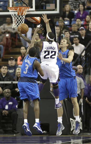 Sacramento Kings guard Isaiah Thomas, center, drives to the basket between Dallas Mavericks' Rodrigue Beaubois, left, of France, and Dirk Nowitzki, of Germany, during the first quarter of an NBA basketball game in Sacramento, Calif., Thursday, Jan. 10, 2013. (AP Photo/Rich Pedroncelli