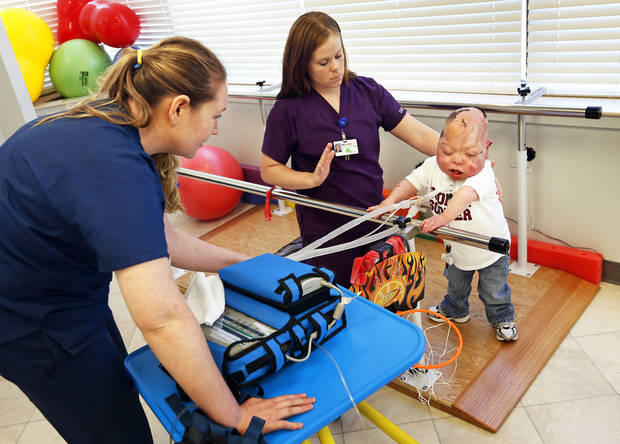 Jennifer Batts, a physical therapy student, left, and Melanie Connel, a physical therapist, work with Fletcher Burns, 8, at The Children�s Center in Bethany. Photos by Nate Billings, The Oklahoman