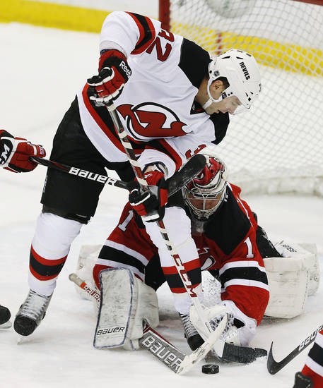New Jersey Devils' Mathiew Darche, top, tries to score against Devils goalie Johan Hedberg (1), of Sweden, during an NHL hockey scrimmage, Wednesday, Jan. 16, 2013, in Newark, N.J. (AP Photo/Julio Cortez)