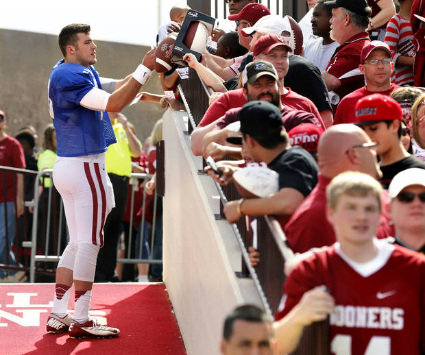 Quarterback Blake Bell signs autographs for fans on his way to the interview room after the annual Spring Football Game at Gaylord Family-Oklahoma Memorial Stadium in Norman, Okla., on Saturday, April 13, 2013. Photo by Steve Sisney, The Oklahoman
