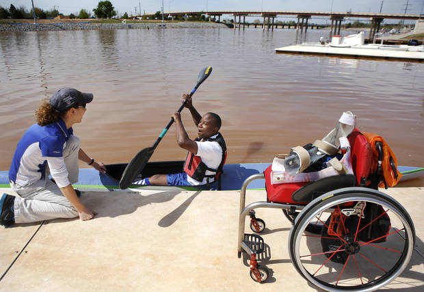 Shad Isaac, 22, gets his paddle in the correct position while Sherry Andrusiak holds his kayak against the dock during a morning practice session for this weekend's USA Canoe/Kayak Trials for Flatwater Sprint.  Photo taken on the Oklahoma River, on  Thursday, April 25, 2013. Photo  by Jim Beckel, The Oklahoman.