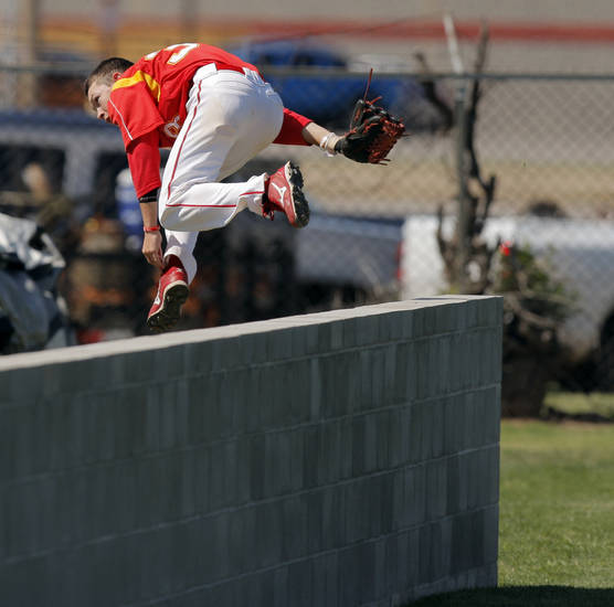 Tanner Nelson (33) of Dale leaps the fence to chase a foul ball during the Class 2A high school baseball championship game between Wister and Dale in Shawnee, Okla., Saturday, May 14, 2011. Wister won, 4-2. Photo by Nate Billings, The Oklahoman