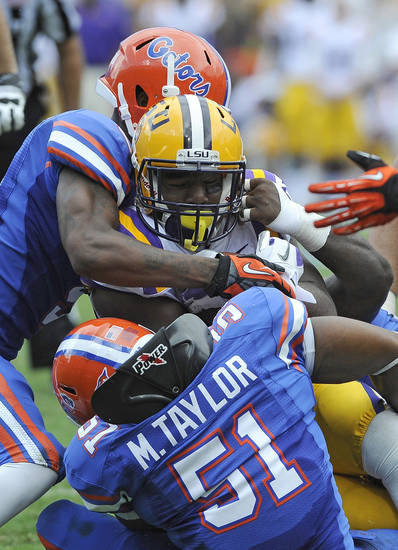 LSU running back Kenny Hilliard, center, is stopped for a short gain by Florida defensive back Marcus Roberson, left, and linebacker Michael Taylor (51) during the first half of an NCAA college football game, Saturday, Oct. 6, 2012, in Gainesville, Fla. (AP Photo/Phil Sandlin)