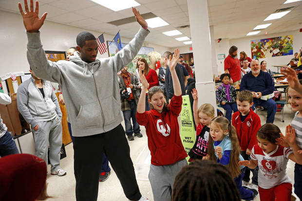 Oklahoma football player Jaz Reynolds and volleyball player Kierra Holst celebrate with a group of children after completing a puzzle during a wellness fair at Jefferson Elementary School in Norman, Okla., Thursday, Jan. 24. 2013. Photo by Bryan Terry, The Oklahoman