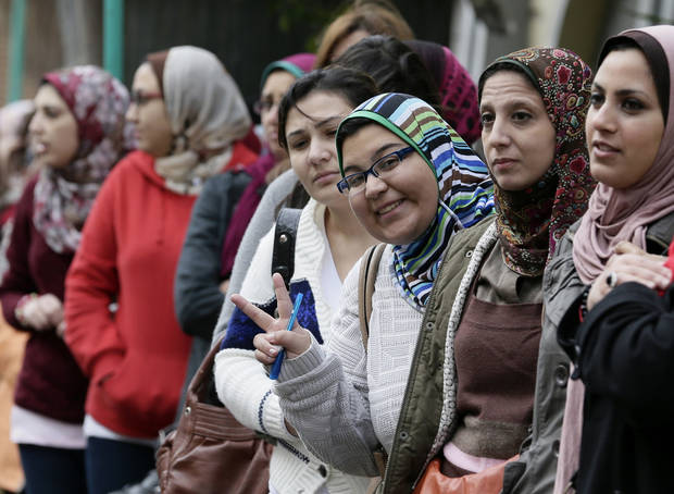 Egyptian women wait to cast their votes outside a polling station during a referendum on a disputed constitution drafted by Islamist supporters of President Morsi, in Alexandria, Egypt, Saturday, Dec. 15, 2012. (AP Photo/Hassan Ammar)