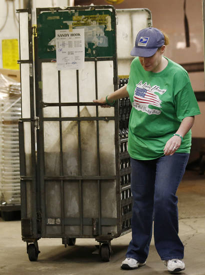 Kelly McLean wears a shirt remembering the families of the victims of the Sandy Hook Elementary School shooting while bringing in mail arriving at the post office, Friday, Dec. 21, 2012, in Newtown, Conn. (AP Photo/Julio Cortez)