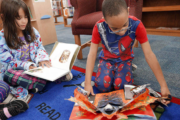 Diana Lopez and Jaisan Johnson read books they received during a Winter Extravaganza at Orvis Risner Elementary in Edmond. Photos by Sarah Phipps, The Oklahoman