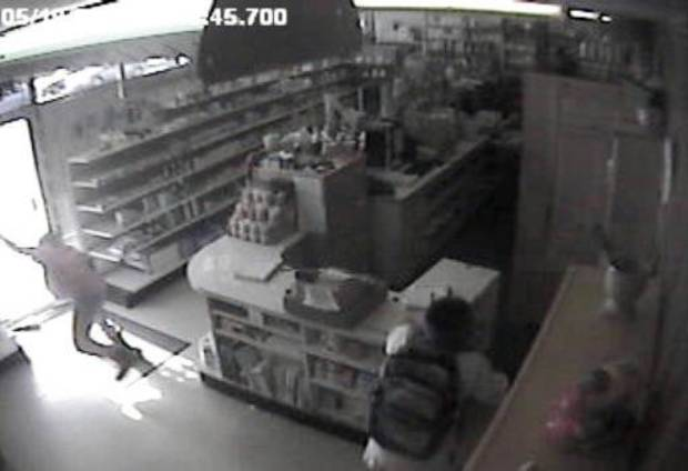 In this image from a 2009 surveillance recording, robber Jevontai Ingram flees out the door of the Reliable Discount Pharmacy in south Oklahoma City while a scond robber, Antwun Parker, is shot as he pulls on a mask. <strong></strong>