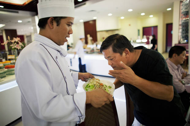 Chef Khai Duong, right, smells and reviews a Sea Bass with Green Chili dish during a multi-course meal prepared by Vo Tung Lam, the executive chef at the Novotal Hotel, who is mentored by Duong. (LiPo Ching/San Joser Mercury News/MCT)