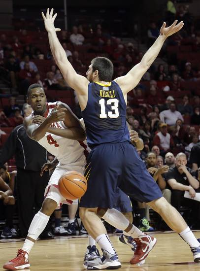 Oklahoma's Andrew Fitzgerald (4) passes the ball past West Virginia 's Deniz Kilicli (13) during the first half of the college basketball game between the University of Oklahoma Sooners (OU) and the West Virginia University Mountaineers (WVU) at the Lloyd Noble Center on Wednesday, March 6, 2013, in Norman, Okla. Photo by Chris Landsberger, The Oklahoman
