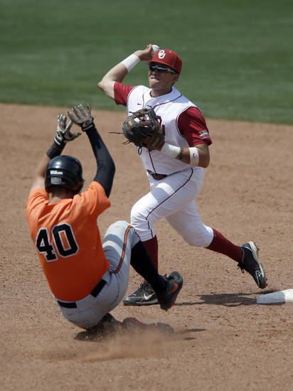 Oklahoma's Hector Lorenzana turns a double play as Oklahoma State's Craig McConaughy slides into second during the Bedlam baseball game between the University of Oklahoma and Oklahoma State University at the Chickasaw Bricktown Ballpark in Oklahoma CIty, Sunday, May 12, 2013. Photo by Sarah Phipps, The Oklahoman