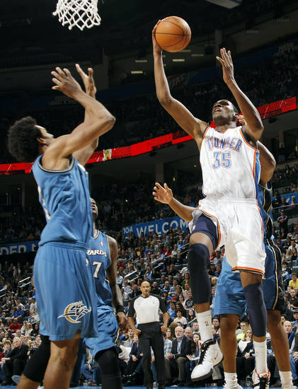 Oklahoma City's Kevin Durant (35) makes a basket after being fouled by Trevor Booker (behind Durant) next to Andray Blatche (7) and Nick Young (1), left, of Washington in double overtime during the NBA basketball game between the Washington Wizards and the Oklahoma City Thunder at the Oklahoma City Arena in Oklahoma City, Friday, January 28, 2011. The Thunder won, 124-117, in double overtime. Photo by Nate Billings, The Oklahoman